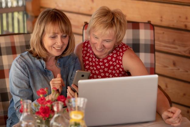 Due donne anziane che usano il laptop a casa, sulla veranda della casa in legno