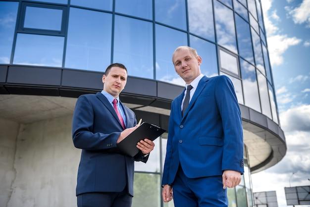 Due uomini d'affari seri in posa contro il business center