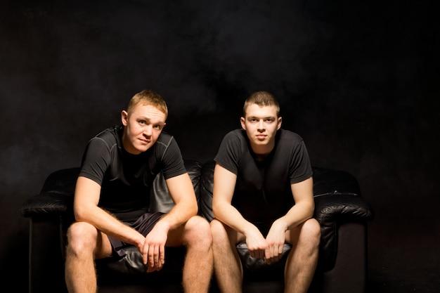 Due giovani uomini in forma seri seduti fianco a fianco su un divano nero