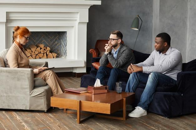 Due uomini seri seduti sul divano e ascoltando la conclusione dello psicologo durante la terapia in ufficio