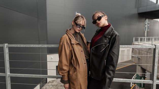 Due giovani belle donne serie modellano in giacca di pelle oversize alla moda con maglione e jeans neri con occhiali da sole vintage in posa in città