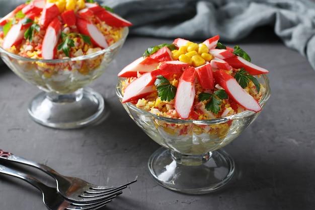 Due porzioni di insalata con bastoncini di granchio, uova e mais in ciotole di vetro trasparente su sfondo scuro.