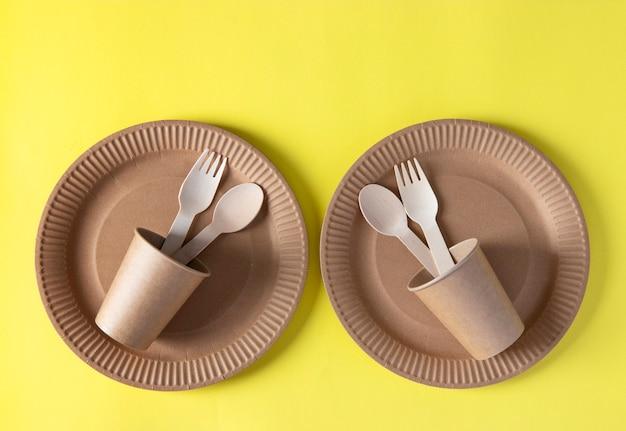 Due set di stoviglie biodegradabili usa e getta di carta artigianale e legno - piatti, forchette, cucchiai, bicchieri su sfondo giallo. rifiuti zero. vista dall'alto.