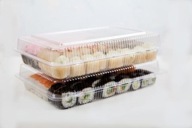 Due set di sushi in contenitori di plastica su un piatto bianco. consegna rotoli.