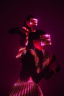 Due ballerine da discoteca sexy si muovono in costumi uv. feste e balli.