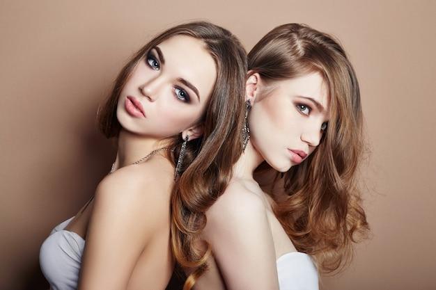 Due giovani ragazze bionde di modo sexy che abbracciano, capelli perfetti, orecchini in gioielli di orecchie sul collo, occhi belli. cura della pelle estiva, occhi belli