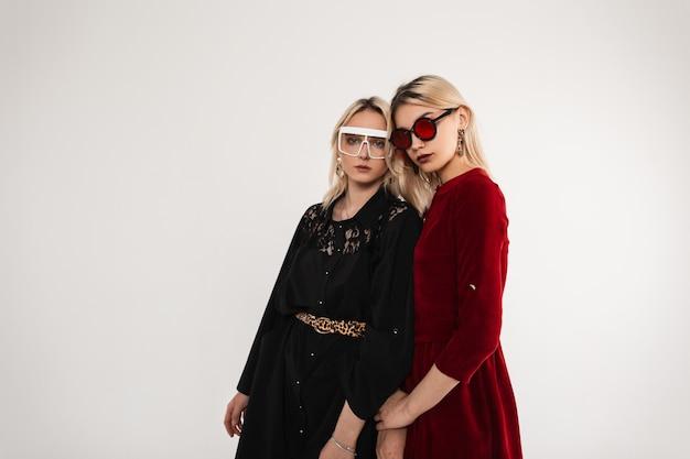Due ragazze sexy alla moda con occhiali da sole alla moda che indossano un abito vintage