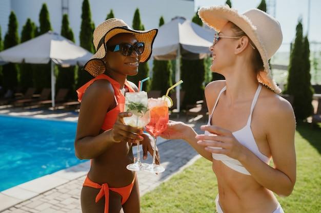 Due amiche sexy bevono cocktail in piscina. persone felici che si divertono durante le vacanze estive, feste a bordo piscina all'aperto. tempo libero per le donne al resort