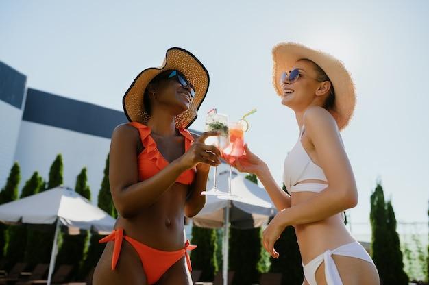 Due amiche sexy bevono cocktail in piscina. persone felici che si divertono durante le vacanze estive, feste a bordo piscina all'aperto. tempo libero delle donne