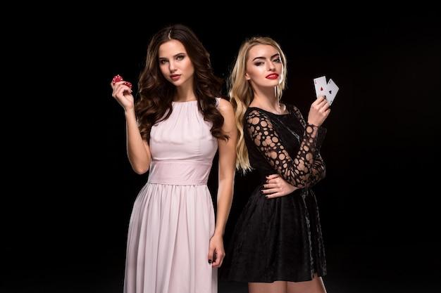 Due ragazze sexy brune e bionde, in posa con patatine in mano, concetto di poker sfondo nero