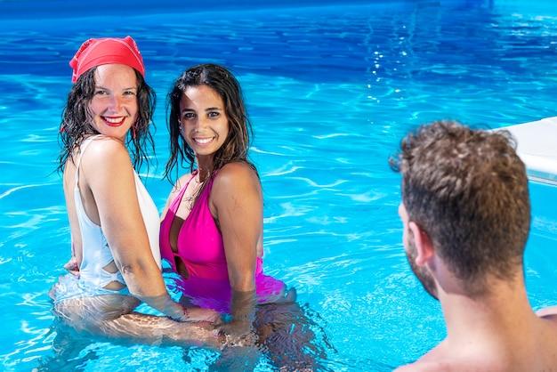 Due ragazze sexy abbracciate in una piscina