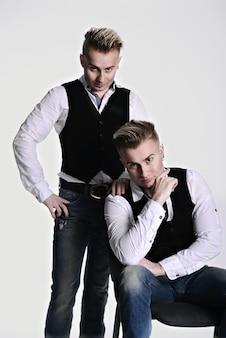 Due fratelli gemelli sexy guardano la telecamera in modo serio e brutale. su uno sfondo bianco. gilet e jeans.