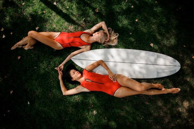 Donna sexy due in costumi da bagno rossi che si trovano vicino ad un wakeboard bianco su erba verde