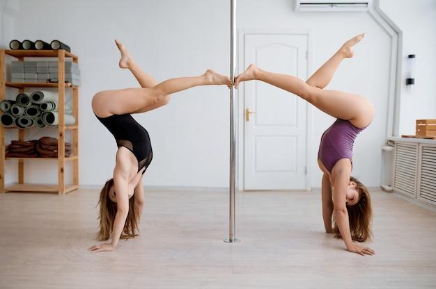 Due donne sexy praticano la pole dance, si allenano in classe