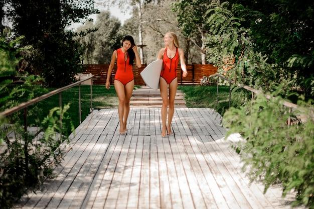 Due donne sexy in costume da bagno rosso che camminano insieme sul ponte