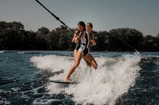 Due donne sexy che praticano il surfing su un bordo giù l'acqua blu