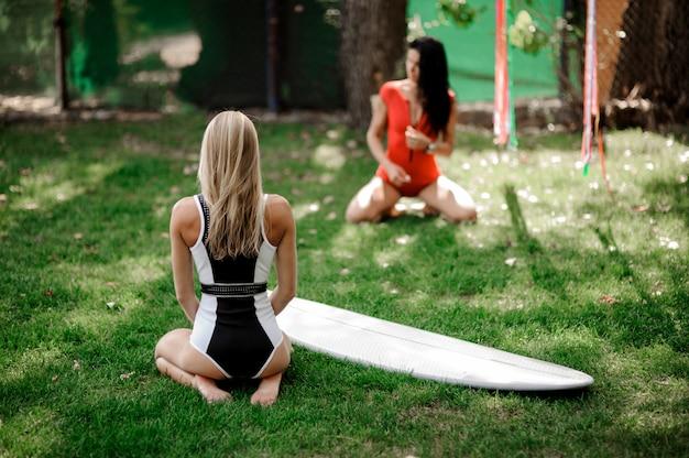 Due giovani donne sexy che si siedono sull'erba verde con il wakeboard