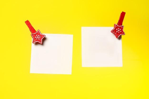 Due fogli di carta bianca appuntati con uno sfondo giallo di molletta di natale un posto da copiare