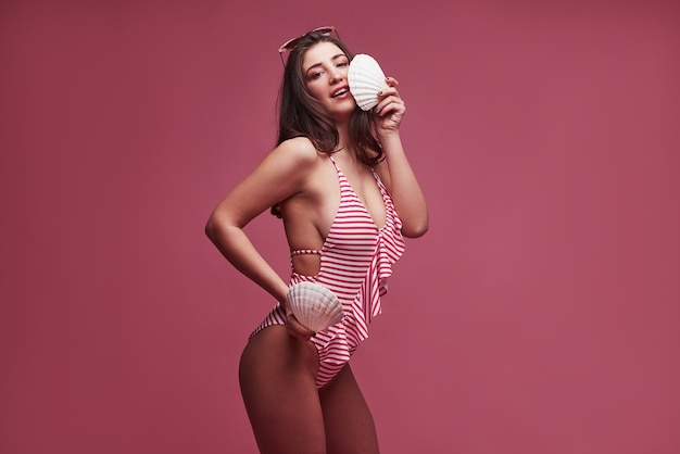 Due crostacei nelle mani. elegante bella ragazza in bikini si leva in piedi e in posa