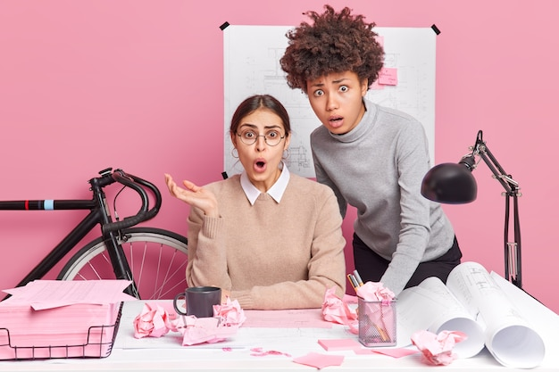 Due donne scioccate che lavorano in ufficio realizzano grandi errori nei progetti di lavoro sulla pianificazione creativa e godono di una posa di partnership vicino al dekstop con i documenti in giro. ingegneri esperti che fanno brainstorming insieme