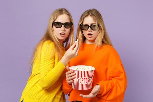Due giovani sorelle gemelle bionde scioccate in occhiali 3d imax che guardano film in possesso di popcorn isolato su parete blu viola pastello. concetto di stile di vita familiare di persone.