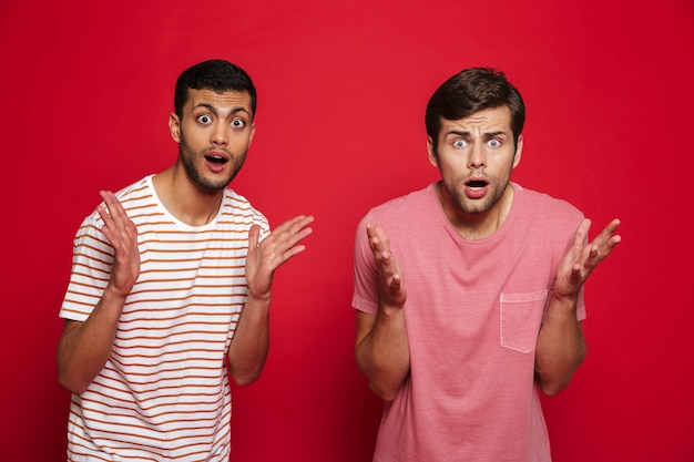 Due giovani scioccati in piedi isolato sopra il muro rosso, scrollando le spalle Foto Premium