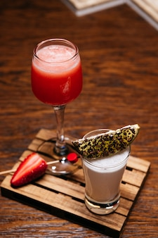 Due shot cocktail con lime e fragole sulla tavola di legno