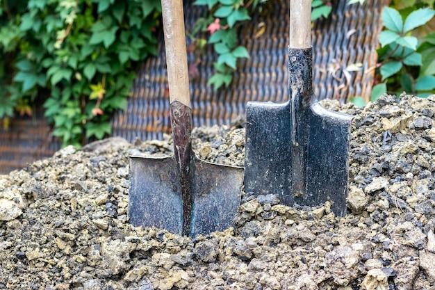 Due pale conficcate nel terreno, un mucchio di terra e una paletta