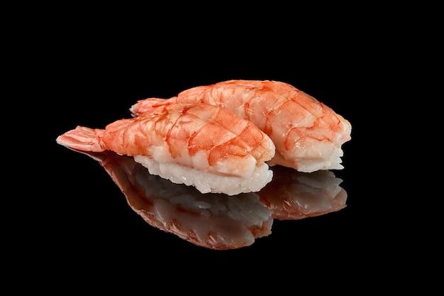 Due nigiri sushi di gamberi su superficie nera con riflesso with