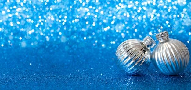 Due palle di natale d'argento su sfondo blu astratto con bokeh e copia spazio.