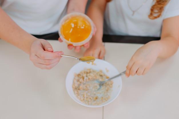 Due sorelle aggiungono il miele alla farina d'avena in cucina.