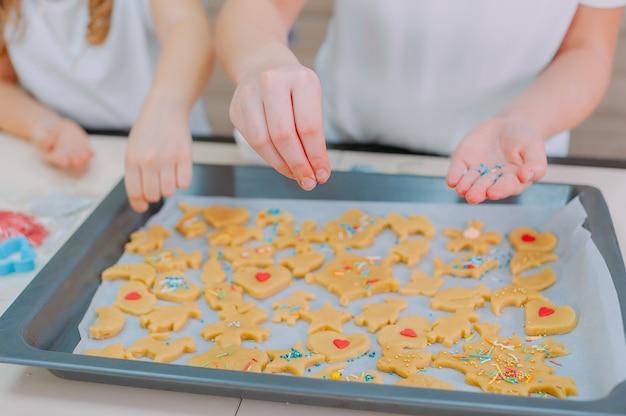 Due sorelle stanno preparando biscotti fatti in casa in cucina.
