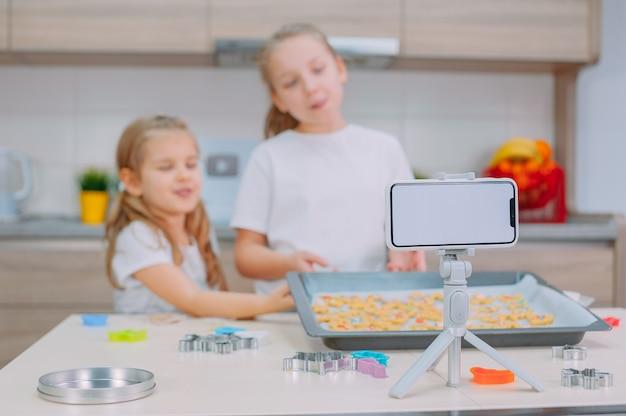 Due sorelle blogger stanno preparando biscotti e filmando video di formazione su uno smartphone.