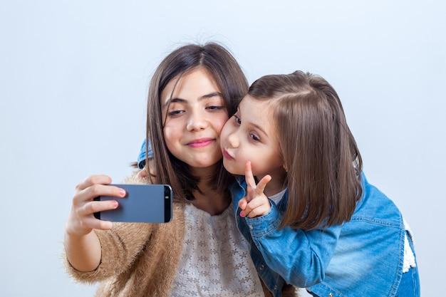 Due sorelle di età diverse si scattano un selfie in uno studio fotografico.
