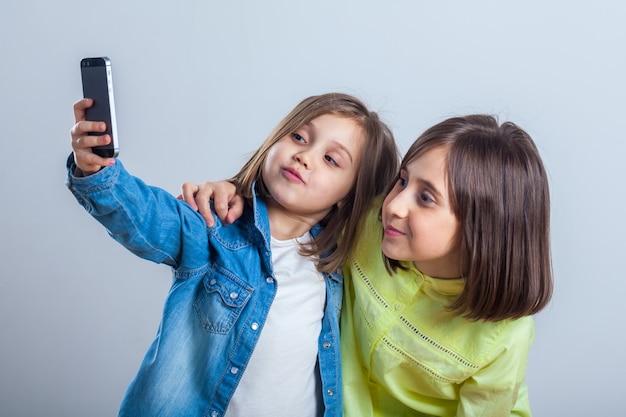 Due sorelle in posa e scattare selfie in studio.