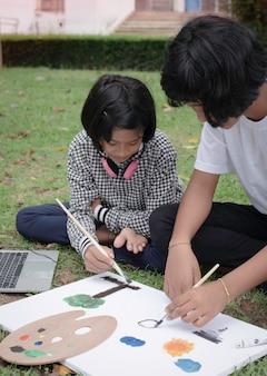 Due sorelle che si siedono sul pianterreno dell'erba verde. colore della pittura su tela, con sensibilità felice, buon hobby. fare attività insieme