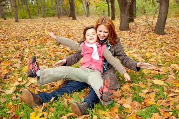 Due sorelle che si siedono sui fogli nel parco. colpo esterno.