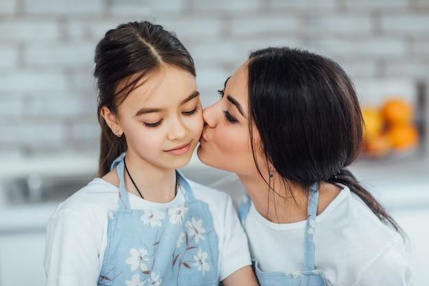 Due sorelle indossano il grembiule mentre cucinano in cucina