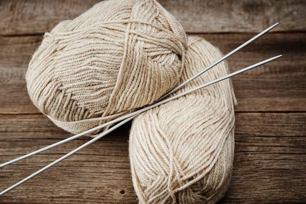 Due matassine di filato di lana e aghi per maglieria su un tavolo di legno