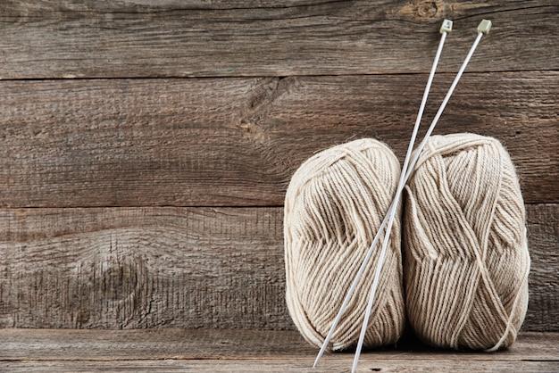 Due matassine di filato di lana e aghi per lavorare a maglia su legno