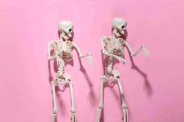Due scheletri sul rosa brillante. decorazione di halloween, tema spaventoso