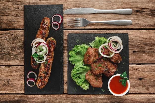 Due bistecche con gustosa carne alla griglia decorata con insalata e anelli di cipolla, servite con salsa di pomodoro. vista dall'alto.