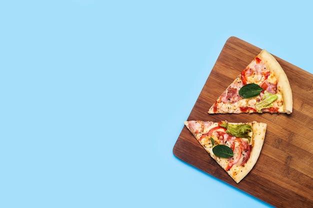 Due fette di pizza fresca calda si trovano su una tavola di legno su un blu