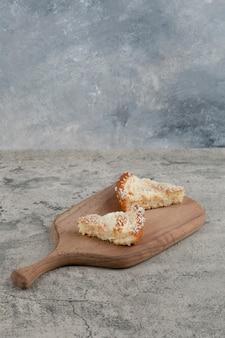 Due fette di torta con granelli di cocco su tavola di legno.