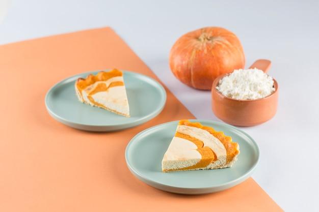 Due fette di cheesecake alla zucca su piatti blu piatti