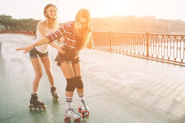 Due giovani donne e pattini a rotelle esili e sexy