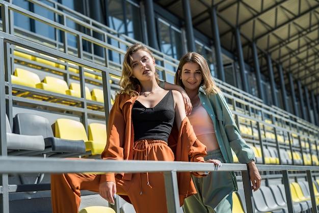 Due giovani donne snelle e sportive si rilassano dopo l'esercizio seduti sui sedili dello stadio. uno stile di vita sano