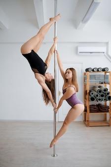 Due donne magre in allenamento con la pole dance. le ragazze con un corpo perfetto mostrano uno stretching eccellente in classe