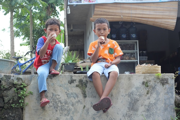Due bambini piccoli seduti e bevono insieme