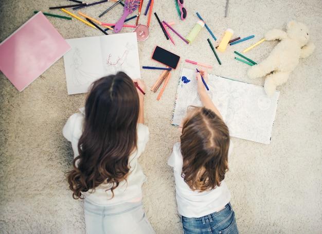 Due bambine sdraiato sul tappeto e disegno. hanno matite e carta bianca su tutto il pavimento.